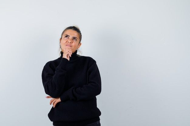 Giovane donna in piedi nel pensiero posa in maglione dolcevita nero e guardando pensieroso, vista frontale.