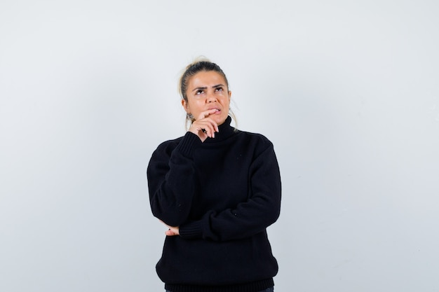 Young female standing in thinking pose in black turtleneck sweater and looking pensive. front view.