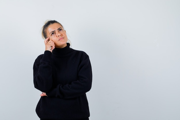 Young female standing in thinking pose in black turtleneck sweater and looking pensive , front view.