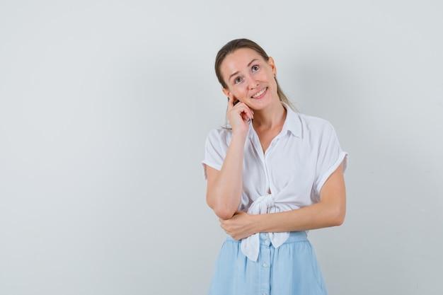 Giovane donna in piedi nel pensiero posa in camicetta e gonna e sembra sognante