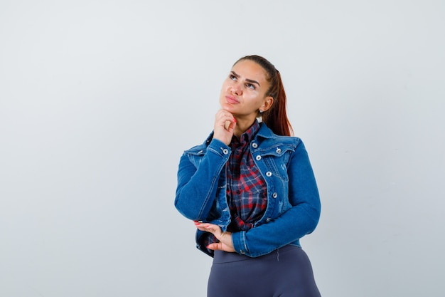 Young female standing in thinking pose in checkered shirt, jacket, pants and looking pensive , front view.