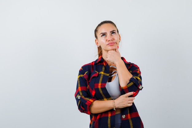 Young female standing in thinking pose in crop top, checkered shirt and looking pensive , front view.
