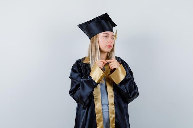 Giovane donna in piedi in posa di pensiero in uniforme laureata e guardando triste
