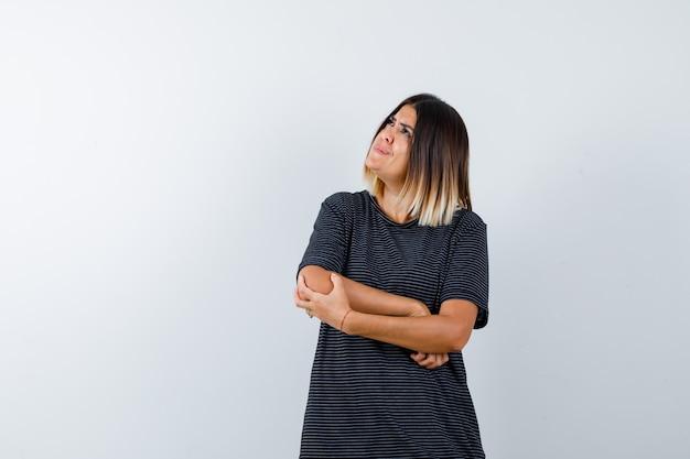 Giovane donna in piedi nel pensiero posa in abito polo e guardando pensieroso. vista frontale.