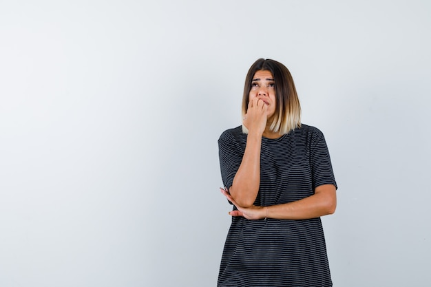 Giovane donna in piedi nella posa di pensiero in abito polo e guardando pensieroso, vista frontale.