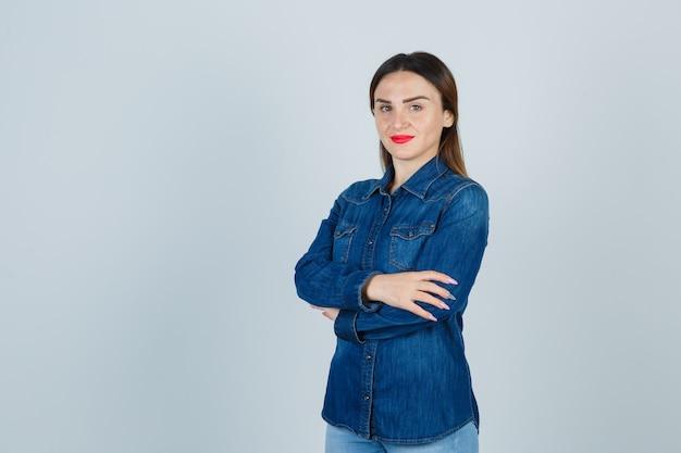 Молодая женщина стоит со скрещенными руками в джинсовой рубашке и джинсах и выглядит уверенно