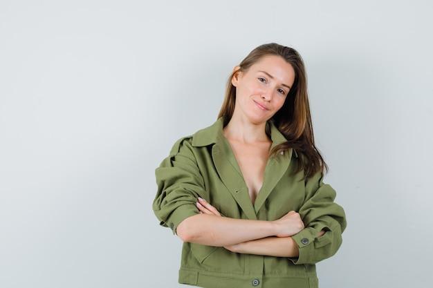 녹색 재킷에 팔을 교차 서서 유쾌한, 전면보기를 찾고 젊은 여성.