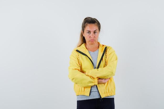 Молодая женщина, стоящая со скрещенными руками в куртке, футболке и задумчиво. передний план.