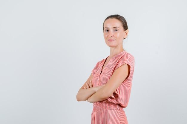 Молодая женщина стоит со скрещенными руками в полосатом платье и выглядит позитивно. передний план.