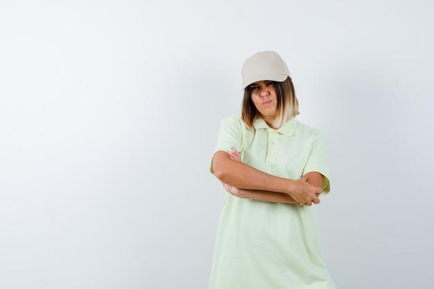 T- 셔츠, 모자에 교차 팔으로 서 젊은 여성과 자신감을 찾고. 전면보기.