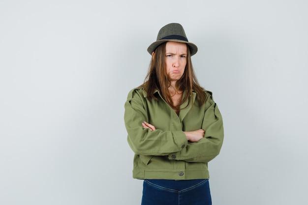 Giovane donna in piedi con le braccia incrociate in giacca, pantaloni, cappello e guardando offeso, vista frontale.