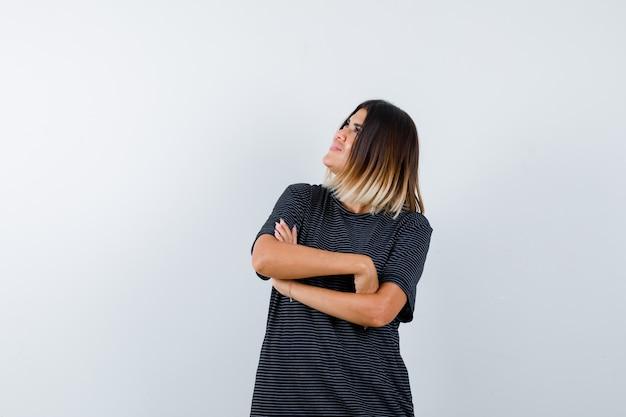 ポロドレスで見上げて、思慮深く、正面図を見ながら、腕を組んで立っている若い女性。