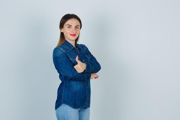 デニムシャツとジーンズで親指を表示し、自信を持って見ながら腕を組んで立っている若い女性