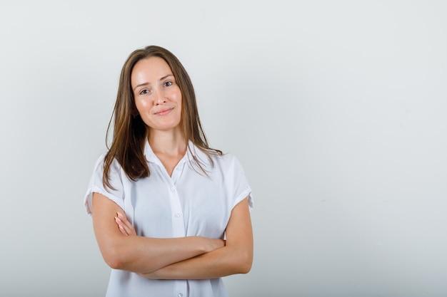 Giovane donna in piedi con le braccia incrociate in camicetta bianca e bellissima.