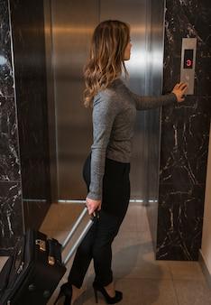 Молодая женщина стоя с чемоданом нажатием кнопки для лифта