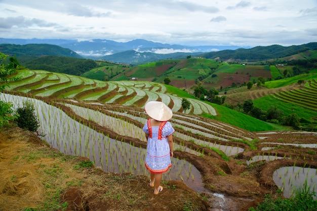 Молодая женщина стоит и смотрит на рисовое поле путешественник в шляпе, наслаждаясь прекрасным видом на рисовое поле