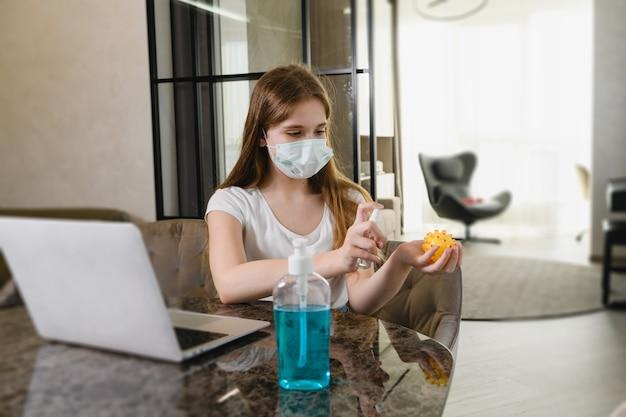 젊은 여성은 세계 전염병 검역 기간 동안 집에 머물고, 보호 마스크를 착용하고, 노트북, 개 장난감, 손에 방부제를 사용합니다