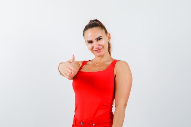 Mano di allungamento della giovane femmina per il saluto in canotta rossa, pantaloni e bella vista frontale.