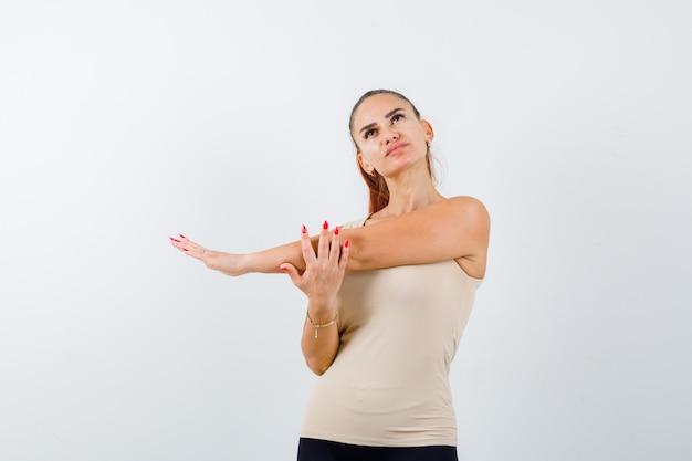 Молодая женщина растягивает верхнюю часть тела в бежевой майке и выглядит расслабленной, вид спереди.
