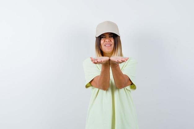 젊은 여성 스트레칭 t- 셔츠, 모자와 귀여운 찾고 손을 cupped. 전면보기.