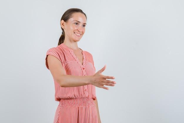 Молодая женщина протягивает руку для тряски в полосатом платье и выглядит весело, вид спереди.