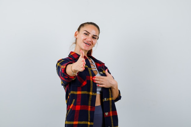Young female stretching hand for greeting in crop top, checkered shirt and looking happy , front view.