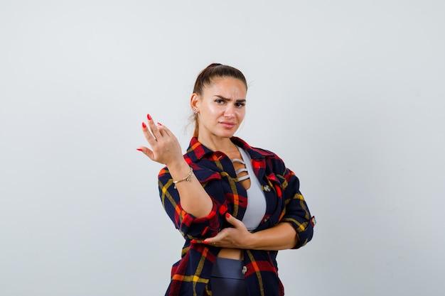 若い女性が手を伸ばしてクロップトップ、市松模様のシャツ、真剣に見えるジェスチャー、正面図でジェスチャーを質問します。