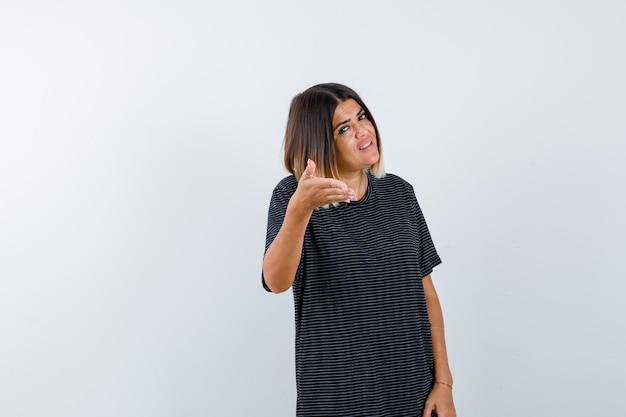 Giovane femmina che allunga la mano nel gesto interrogativo in vestito da polo e che sembra felice, vista frontale.