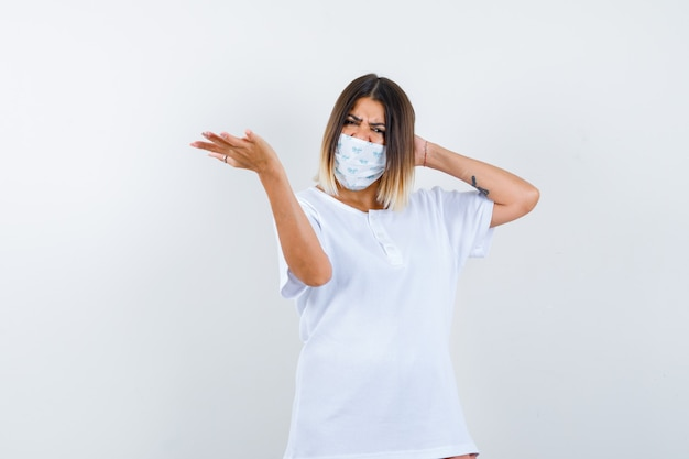 Young female stretching hand in questioning gesture in t-shirt, mask and looking hesitant , front view.