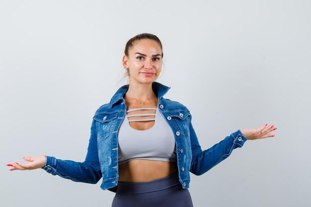 Молодая женщина протягивает руки в укороченном топе, куртке, брюках и выглядит уверенно, вид спереди.