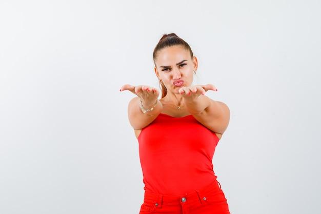 赤いタンクトップ、パンツで何かを与えて、かわいく見えるために手を伸ばす若い女性。正面図。
