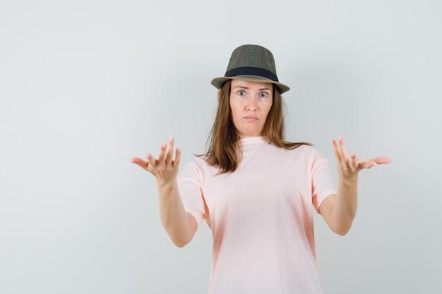 분홍색 티셔츠, 모자 전면보기에 의아해 제스처에 손을 스트레칭하는 젊은 여성.