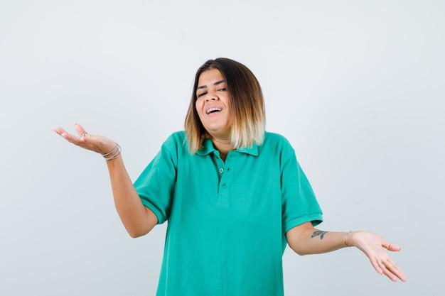 Giovane femmina che allunga le mani in modo interrogativo in maglietta polo e sembra felice. vista frontale.