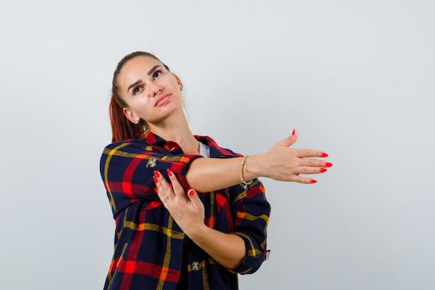 クロップトップ、市松模様のシャツで上半身を伸ばし、リラックスして見える若い女性。正面図。