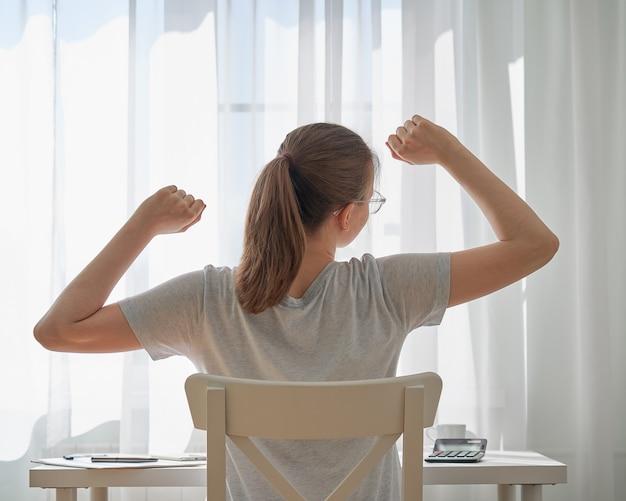 Молодая женщина растягивается, сидя за столом дома, проблемы удаленной работы и дискомфорт
