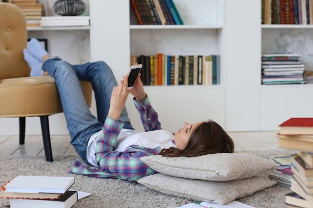 공부하기 전에 소셜 미디어를 확인하는 젊은 여학생, 책 더미로 둘러싸인 아늑한 국내 인테리어에 대해 바닥에 누워.