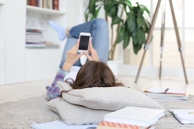 勉強に戻る前にソーシャルメディアをチェックしている若い女子学生は、本の山に囲まれ、居心地の良い国内のインテリアに対して床に横たわっています。