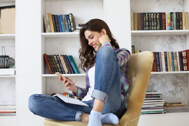 勉強に戻る前にソーシャルメディアをチェックし、本の山に囲まれた居心地の良い国内のインテリアに対して椅子に座っている若い女子学生。