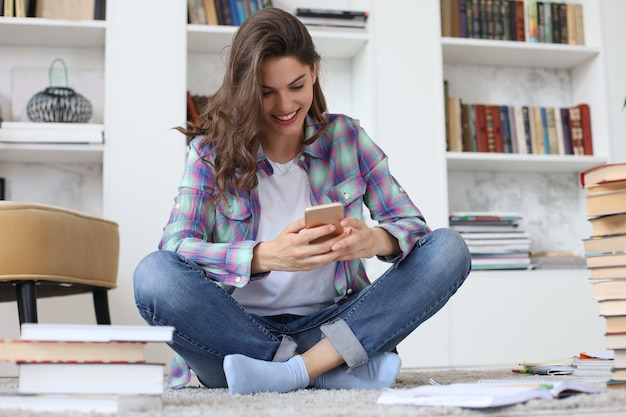 젊은 여학생은 공부하기 전에 소셜 미디어를 확인하고 책 더미로 둘러싸인 아늑한 실내 인테리어에 기대어 바닥에 앉아 있습니다.