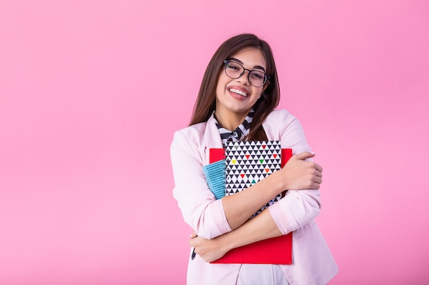 Young female student in glasses holding books in hand isolated on pink wall portrait, casual daily lifestyle student holding notebooks smiling