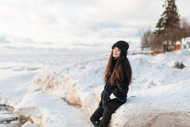 Young female student in hat enjoying winter