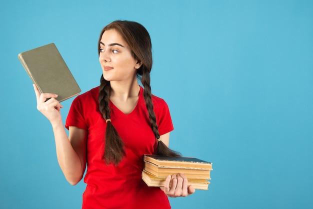 Молодая студентка в красной футболке с книгами, стоящими на синей стене.