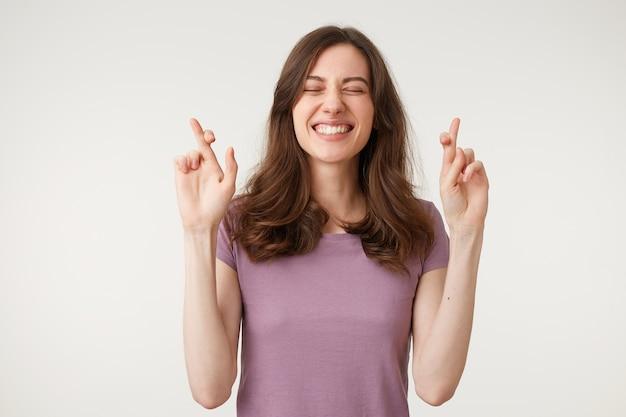 Giovane studentessa tenendo le dita incrociate e gli occhi chiusi per esprimere un vecchio desiderio