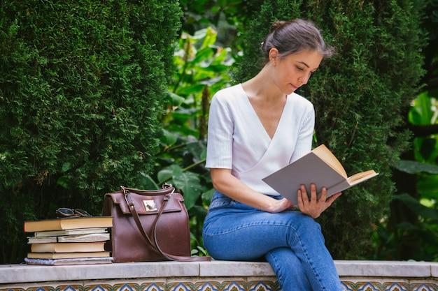 Молодая студентка, изучающая учебную книгу