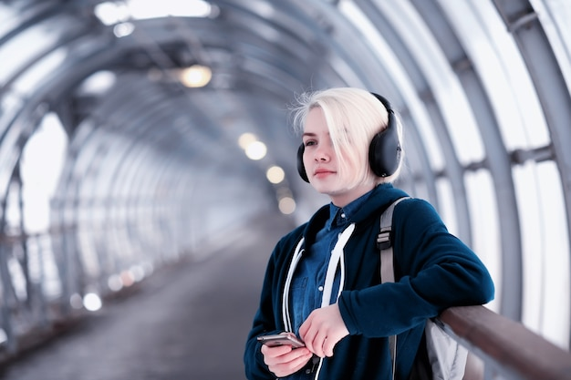 Young female student listening to music in big headphones in the subway tunnel