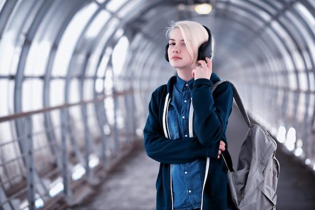 Молодая студентка слушает музыку в больших наушниках в туннеле метро