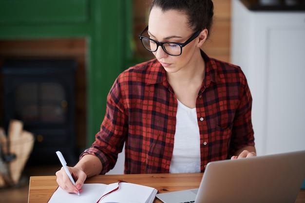 Молодая студентка онлайн-курса обучения, делая заметки, сидя за столом перед ноутбуком дома