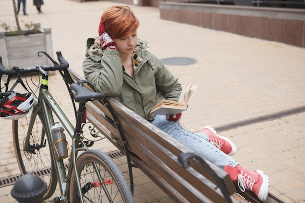도시에서 자전거를 타고 휴식을 취하고 책을 읽는 젊은 여성 학생