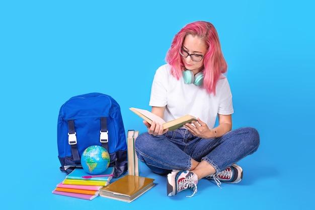 Молодая студентка, читающая книги, сидя на полу с рюкзаком на фоне синего цвета. счастливая студентка сидит с рюкзаком, книгами, наушниками. концепция образования, copyspace