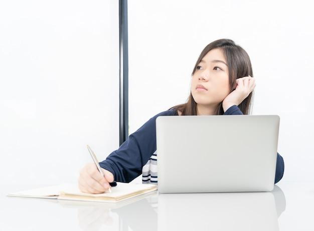 リビングルームに座っているとオンライン学習の若い女子学生